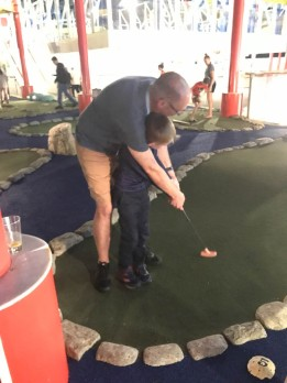 Uncle Evan teaching Andrew how to play mini golf